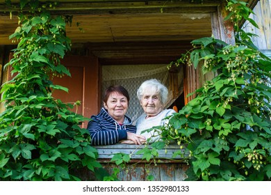 Elderly woman and her adult daughter looking out the village house.