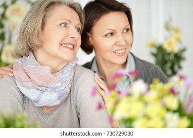 An elderly woman with her daughter looking away