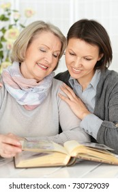 an elderly woman with her daughter reading a book