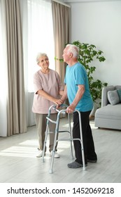 Elderly woman and her husband with walking frame indoors