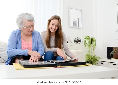 elderly woman with her young granddaughter at home looking at memory in family photo album