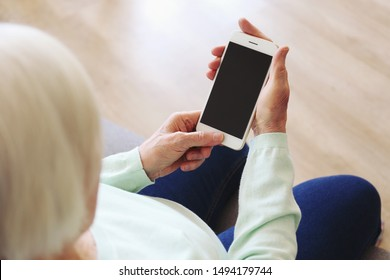 Elderly woman holding blank screen cell phone gadget in hands. Old lady with wrinkled skin trying to vigure out touchscreen smartphone. Background, close up, overhead, top view, copy space.