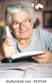 Elderly woman holding a book and looking at camera