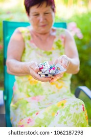 Elderly woman holding daily antidiabetic pills dosage and vitamin.