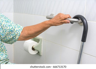 elderly woman holding a grab bars in a bathroom