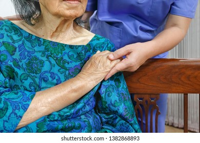 elderly woman holding hand with caregiver