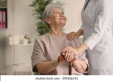 Elderly woman holding hands on walking stick and listening doctor in light room