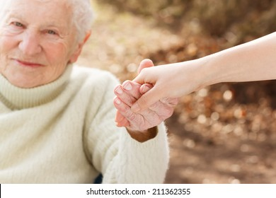 Elderly woman holding hands with young woman outside