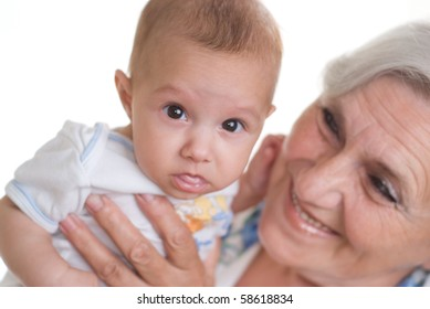 elderly woman holding a newborn in her arms on a white