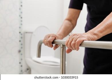 Elderly woman holding on handrail in bathroom.