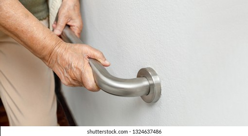 Elderly woman holding on handrail for safety walk steps