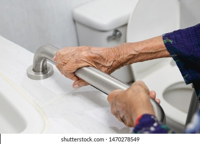 Elderly woman holding on handrail in bathroom