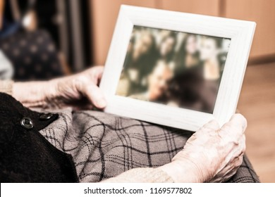 Elderly woman holding a picture frame and watching picture