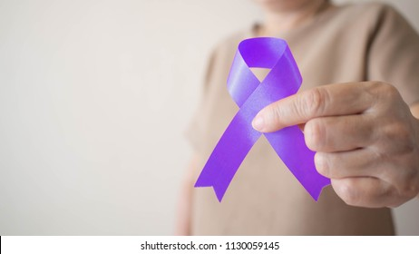 Elderly woman holding purple ribbon awareness w/ copy space. Symbol is used to raise awareness for Alzheimer's disease, elder abuse, epilepsy, pancreatic cancer, thyroid cancer and lupus. Close up.