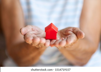 Elderly woman holding a small house in her hands