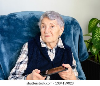 Elderly woman is holding a smartphone. She is hurt and disappointed. She was given this phone and was not taught to use.