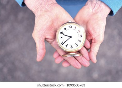 Elderly woman holds an alarm clock in wrinkled hands. Hands of elderly grandmother. Concept of time is not standing still.