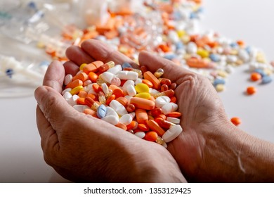 An elderly woman holds a lot of colored pills in old hands on a white background. Painful old age. Health care of older people.