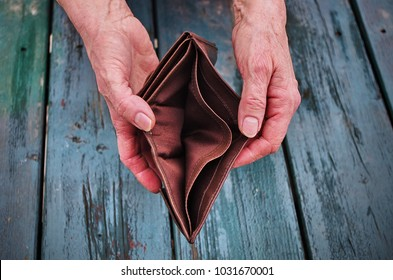 An elderly woman holds an empty purse on wooden vintage table. The concept of poverty in retirement. Global Extreme poverty.No money help me.