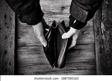 An elderly woman holds an empty purse or wallet on wooden vintage table. Black and white photo.The concept of poverty in retirement. Global Extreme poverty. No money help me. Global Financial crisis.