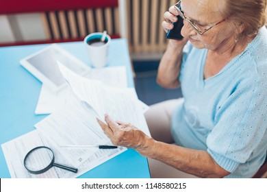 Elderly woman at home contacting custumer services after recieving a bill