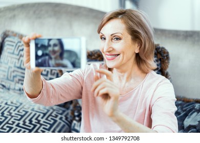 Elderly Woman at Home in the Living Room with a Phone in Her Hands. A Woman Wants to Take a Picture of Herself on the Phone. On the Face of the Woman's Sweet Smile. Close Up Shot.