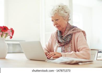 Elderly woman at home typing something using her laptop