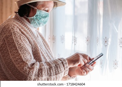 Elderly woman in isolation wearing a medical mask, using mobile phone. Quarantine life