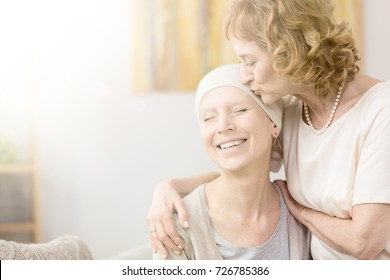 Elderly woman kissing happy cancer survivor's temple, comforting her friend