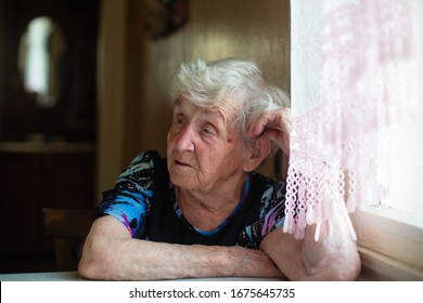 An elderly woman in the kitchen of her house sitting at table.
