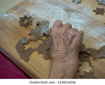 Elderly woman kneading  dough and preparing Christmas cookies. Xmas