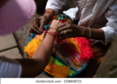 Elderly Woman Knotts the Red Thread on the Wrist Band Tourist