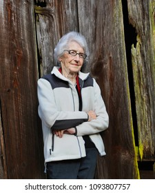 Elderly woman leans against an old wooden barn.  Her face is serene as she remembers her childhood and this old barn.