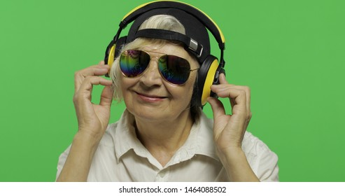 An elderly woman listens to music in headphones. Old pretty happy grandmother in sunglasses and cap. Place for your logo or text.