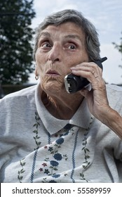 An elderly woman, with a look of surprise on her face, talks on a cordless phone.