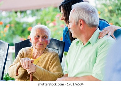 Elderly woman looking to the carer and her son, the visitor.