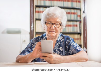 Elderly woman looking at a smart phone at home.