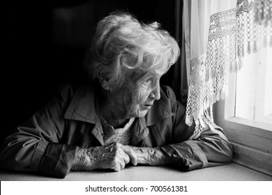 An elderly woman looks longingly out the window.