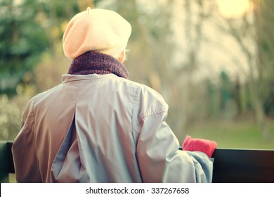 An elderly woman looks off into the distance. Rear view.