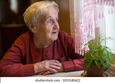 An elderly woman looks out the window.