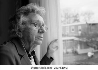 Elderly woman looks out a window
