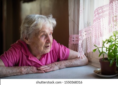 Elderly woman looks sadly out the window.