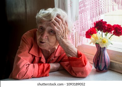 Elderly woman looks sadly sitting near the window.