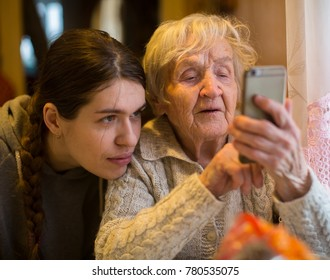 An elderly woman looks at a smartphone, with his adult granddaughter.