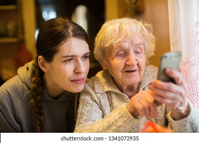 Elderly woman looks and typing on a smartphone, with his adult girl granddaughter.