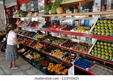 An elderly woman looks vegetables in a public market in Athens, Greece  on July 20, 2015