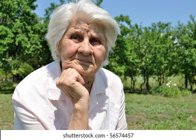 An elderly woman, lost in thought, leaning on the arm, von Garden