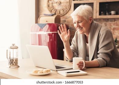 Ältere Frauen, die einen Videoanruf auf Laptop in der Küche tätigen, am Bildschirm winkeln, mit Kindern chatten, freier Platz