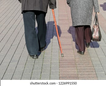 Elderly woman and man with a cane walking down the street, rear view. An elderly couple in warm clothes, concept for old age, diseases of the joints and spine