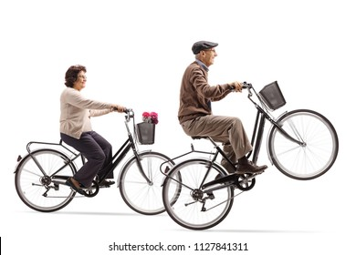 Elderly woman and an elderly man riding bicycles with the elderly man doing a wheelie isolated on white background